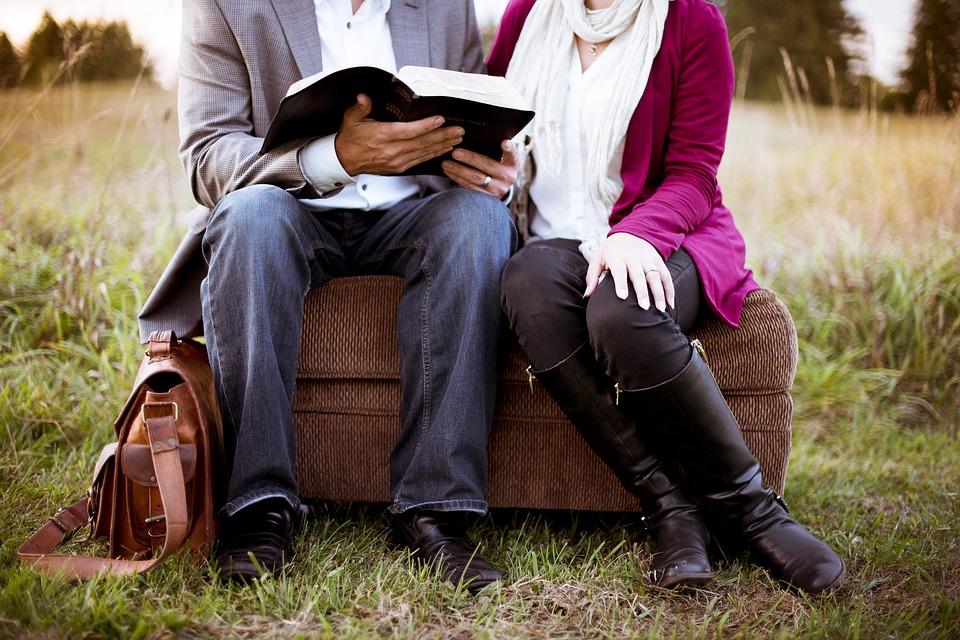 Un home i una dona llegint en un parc