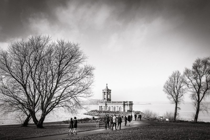 Wedding guests arrive at Normanton Church in Rutland black and white photos