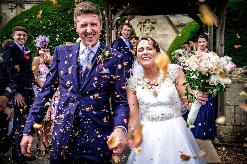 Bride and Groom in a confetti shower at a Somerset Wedding in Holt