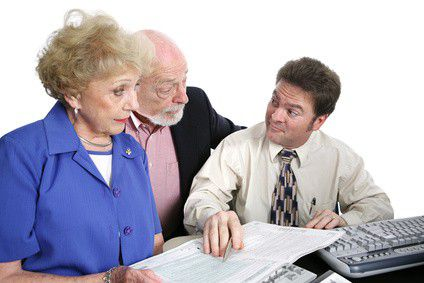 A senior couple going over their taxes with a shady accountant.  He has just suggested something sneaky.  Isolated on white.