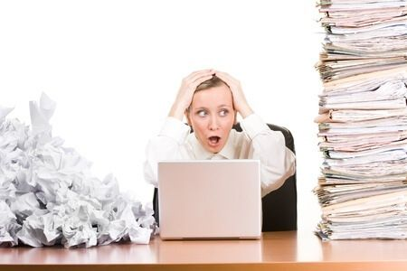 9570920 - a woman sitting at her desk with papers stacked up.