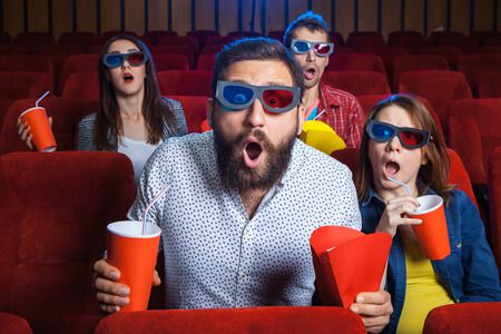 48207935 - a variety of human emotions of friends holding a cola and popcorn in the cinema.