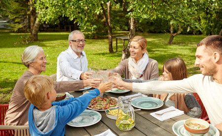 37107069 - family, generation, home, holidays and people concept - happy family having dinner and clinking glasses in summer garden