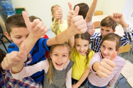34765226 - education, elementary school, learning, gesture and people concept - group of school kids and showing thumbs up in classroom
