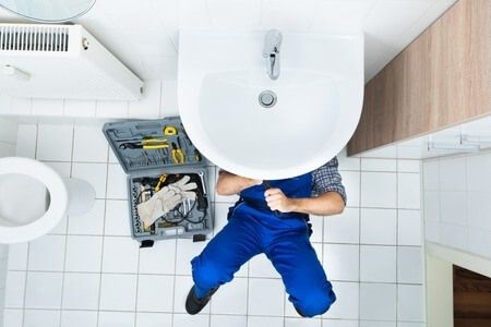 35689919 - high angle view of male plumber repairing a sink in bathroom