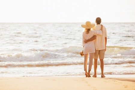 49495424 - happy romantic middle aged couple enjoying beautiful sunset on the beach. travel vacation retirement lifestyle concept.