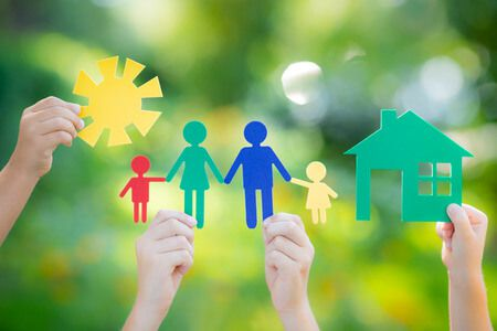 36423159 - paper house and family in hand against spring green background. real estate business concept