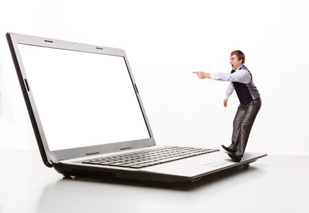 33416413 - afraid man stands on the edge of  laptop and points to monitor