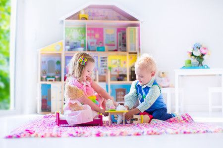 41386600 - kids playing with doll house and stuffed animal toys. children sit on a pink rug in a play room at home or kindergarten. toddler kid and baby with plush toy and dolls. birthday party for little child.