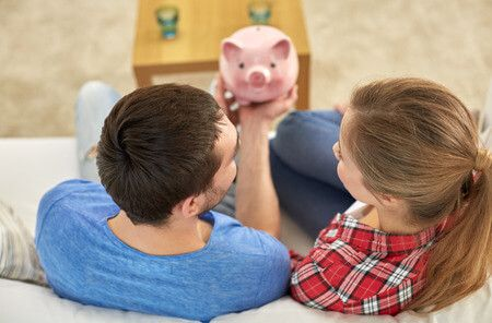 38817506 - money, home, finance and relationships concept - close up of couple with piggy bank sitting on sofa
