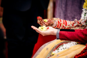 Bride and groom taking part in ceremony traditions and rituals | RR Photographic