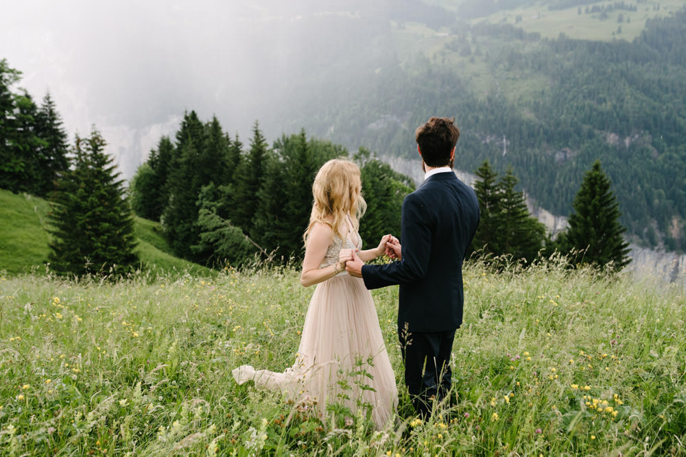 Newly married couple holding hands and looking at the mountains in Wengen, Switzerland
