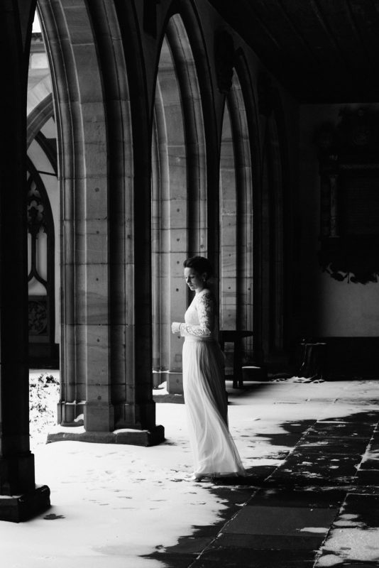 Intimate wedding photography in Basel: Portrait of a bride in her wedding dress at Basel Munster in the snow