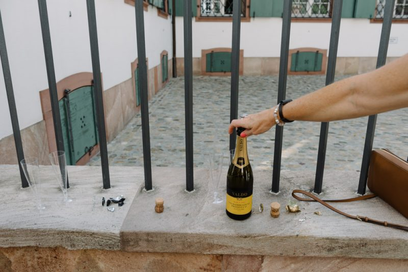 A hand is reaching for a bottle of champagne outside Basel Zivilstandsamt after a wedding