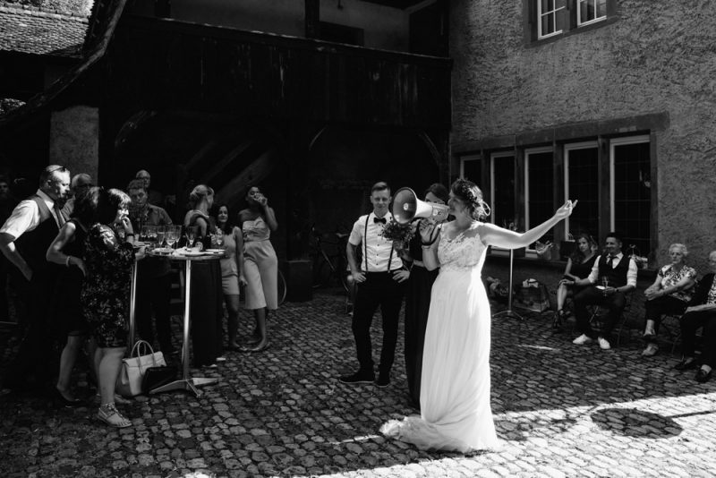 bride giving a speech at her wedding surrounded by friends and family on her wedding day at Ostquai Basel