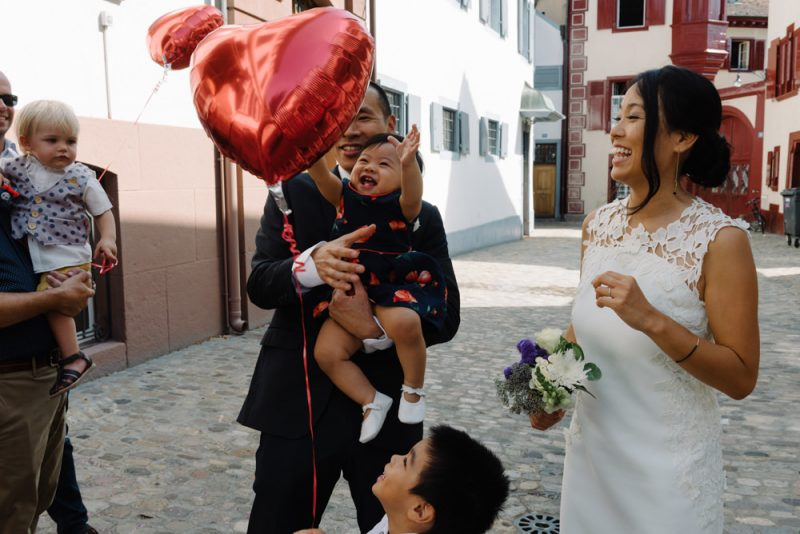 A baby is reaching for a red heart balloon, her parents have just married in Basel registry office. Wedding photography by Caroline Hancox Photography