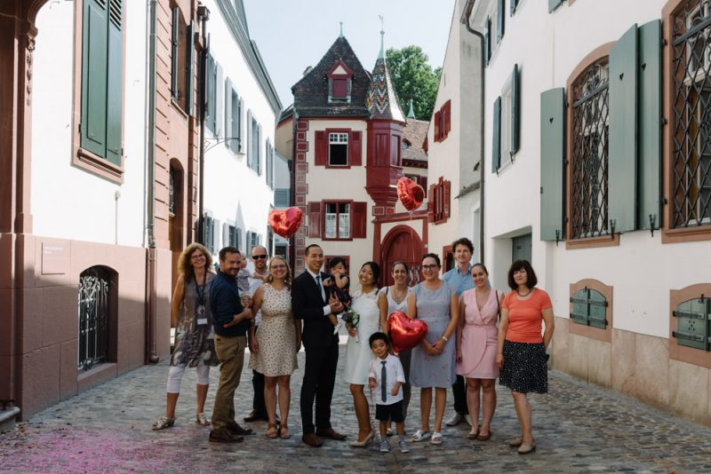 Group photo of all wedding guess with red balloons. At Basel Zivilstandsamt. Swiss Wedding Photographer