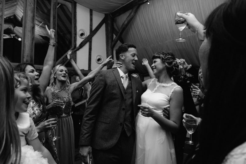 A wedding reception at South Farm near Royston. A couple are dancing at their wedding and their guests are watching and smiling, by Caroline Hancox Photography
