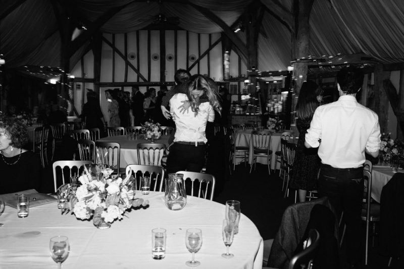 The wedding food has been cleared away and a man is lifting up a woman and spinning her around. It is rustic barn venue