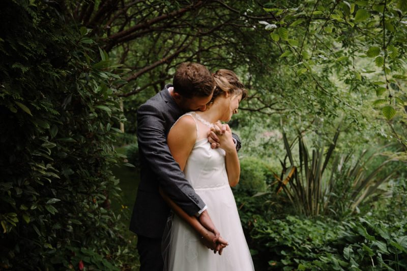 A bride and groom are surrounded by green trees and bushes and he is kissing her on the neck. They are holding hands