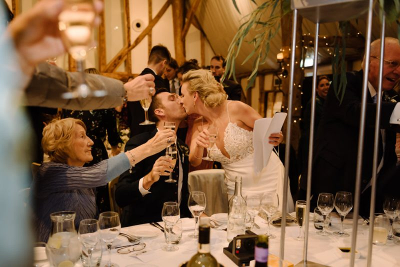 a feminist wedding. A bride is giving a speech and is kissing her partner. Their guests are raising champagne glasses to toast them both