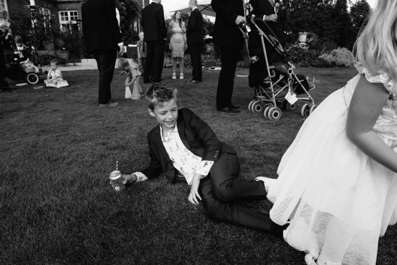 A young boy is at a wedding reception and is lying on the floor with a can of drink. A girl is running out of the frame. The wedding is at Chippenham Hall