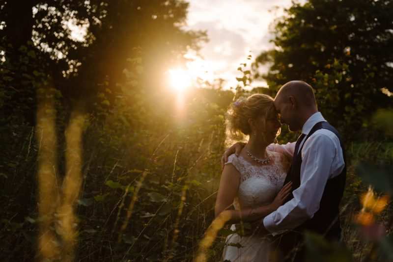 A couple are embracing in a field of grass at sunset in golden light at Chippenham Park