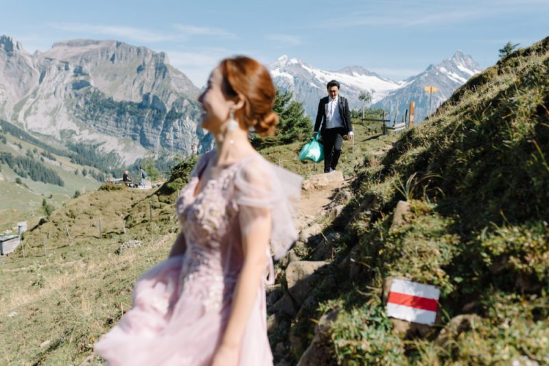 A couple are walking up a mountain together to elope. They are at Schynige Platte and you can see the Eiger mountain in the background.