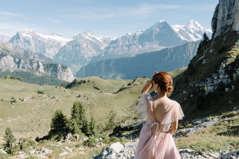A woman in a pink wedding dress is looking at a mountain scene. And is about to elope in Switzerland.