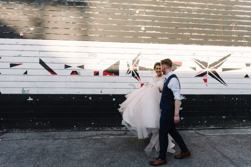 bride and groom in front of some graffiti is in London on their wedding