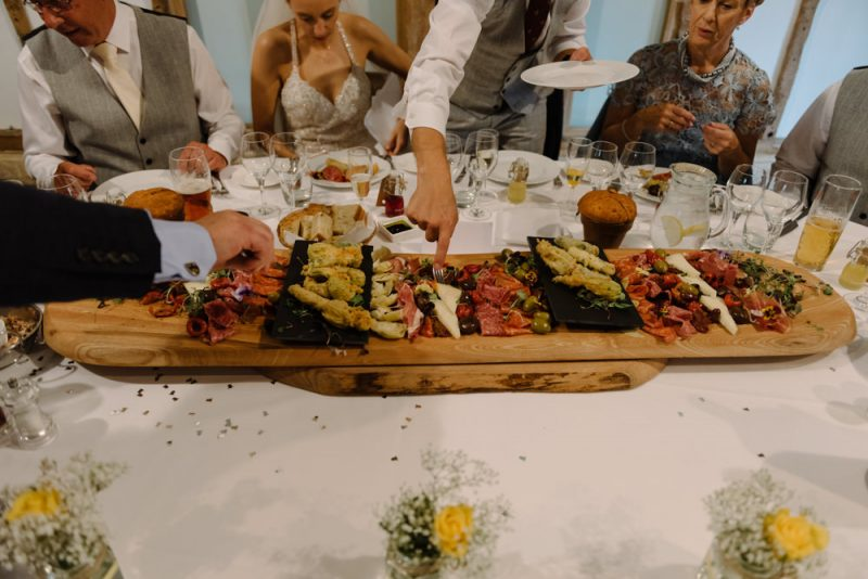 A wedding party sharing a huge platter of cured meats and cheeses, it looks delicious
