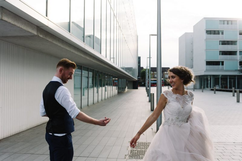 a candid photograph of a bride and groom standing in an urban environment near the Southbank in London.