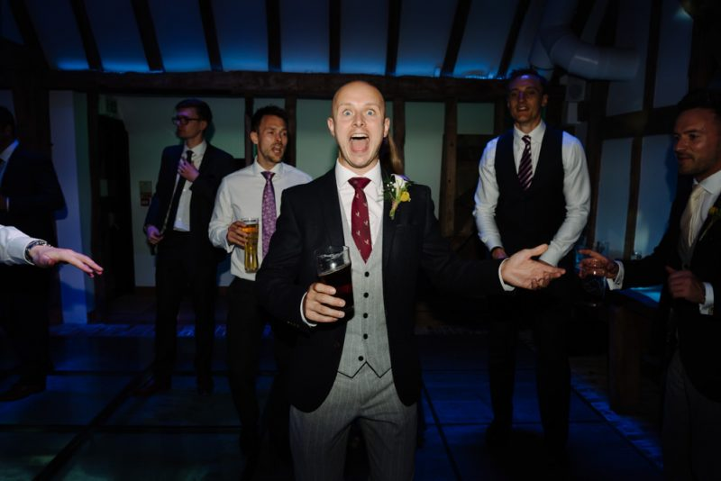 A groom is very happy having a on the dance floor with friends. The wedding is at South Farm