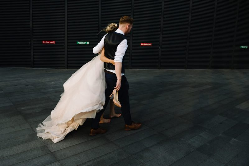 bride is barefoot and her husband is carrying her Christian Louboutin shoes