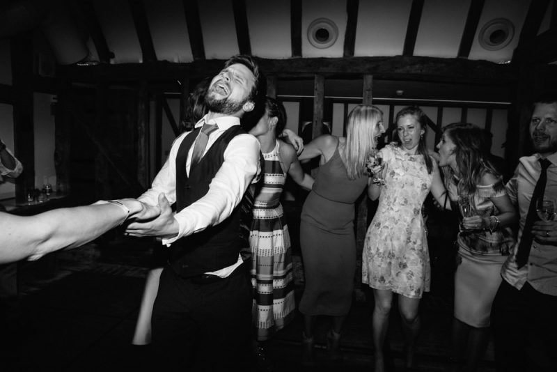 a wedding photograph at South Farm. Guests are dancing on a packed dance floor in the horse barn