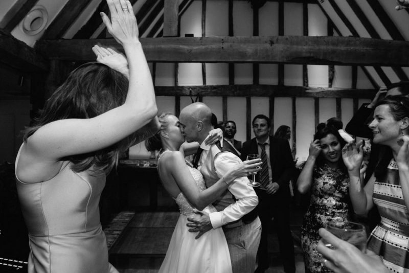 Alternative wedding photography, during the first dance the couple kiss and their guests look on and cheer