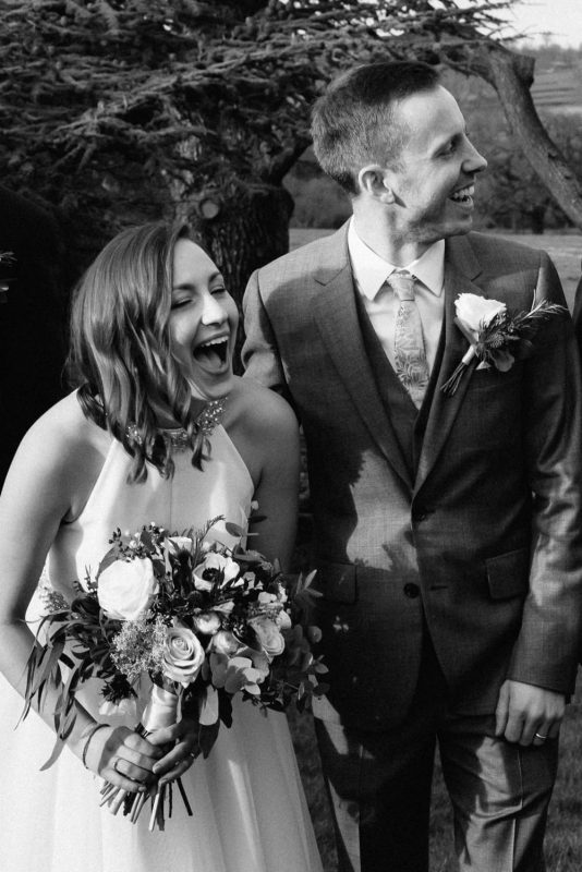 A bride and groom are laughing at the camera and each other