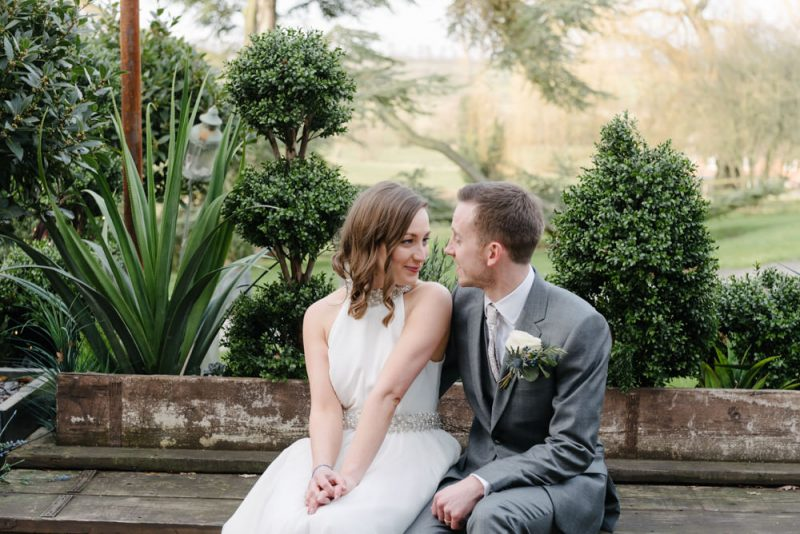 A bride and groom are sitting on a bench in front of some green bushes and are looking and smiling at each other