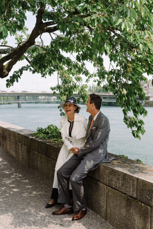 an older couple are posing for wedding photographs. They are laughing and she is wearing a stylish jumpsuit an a straw hat