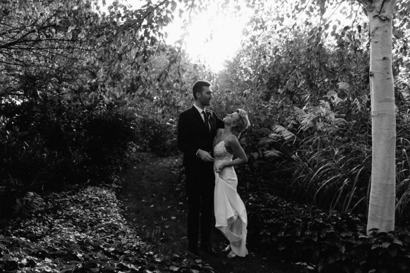 Gorgeous wedding photography: a couple together in a green garden he is looking into her eyes lovingly