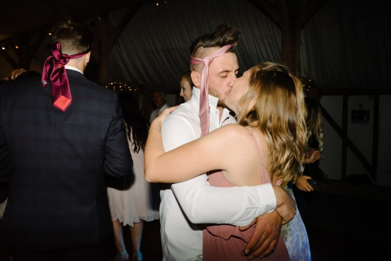 a couple are kissing at the end of a wedding. He has his tie tied around his head