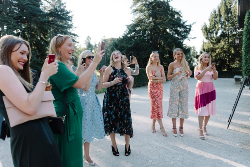 Pretty young women in beautiful dresses are laughing and holding phones taking photos at a wedding