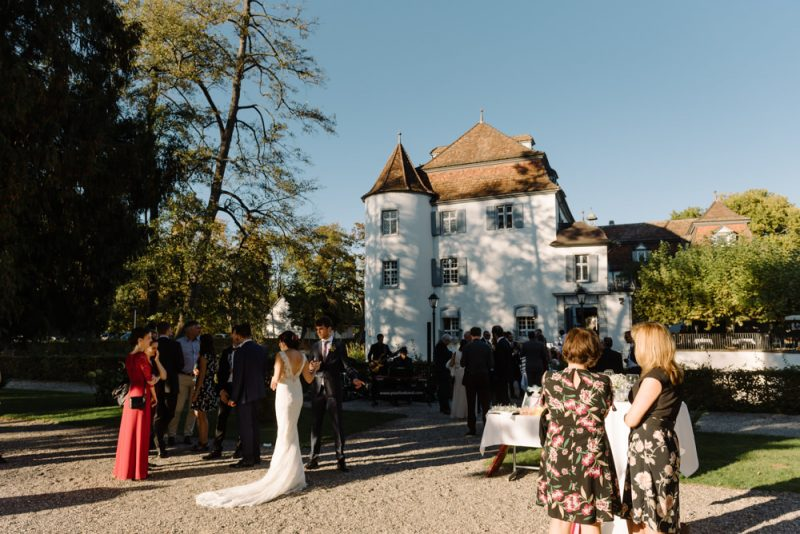 Schloss Binningen wedding, seen in the background while a wedding reception is going on the the foreground.