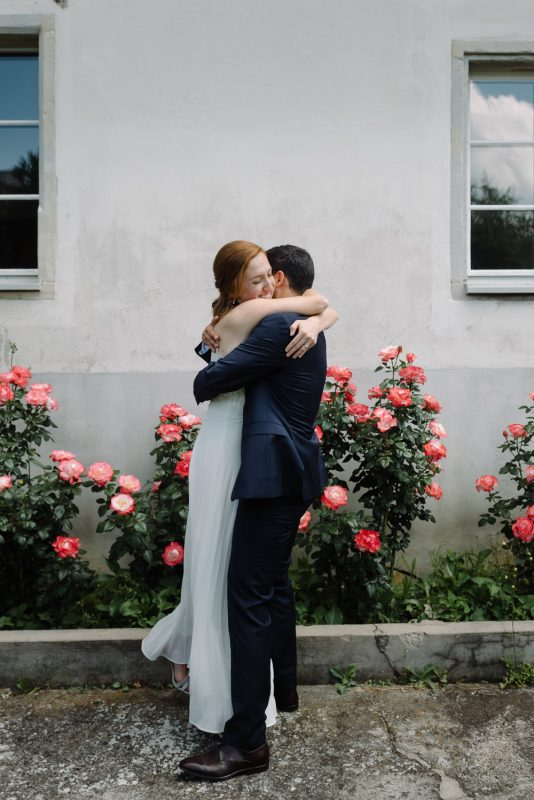 Bride and groom embrace in front of red roses