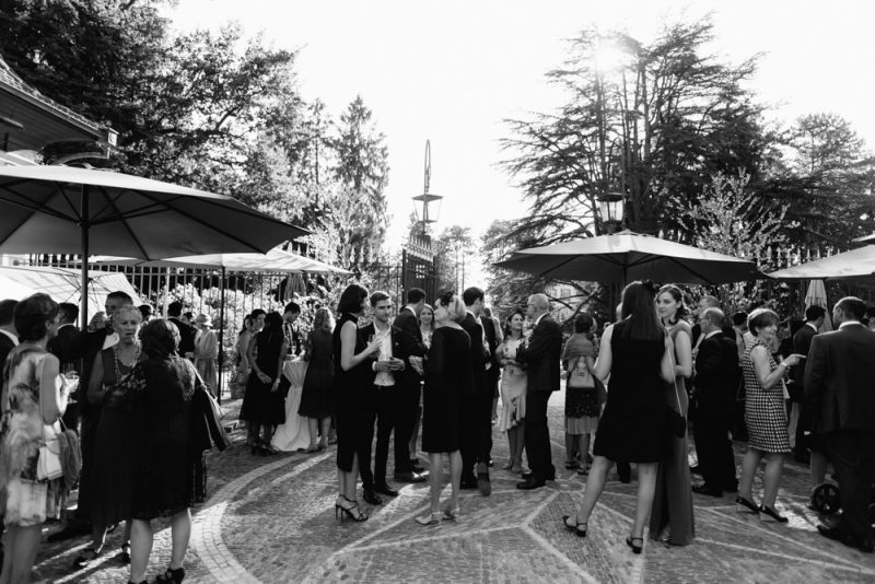 Drinks reception with lots of people celebrating a wedding in the sunshine at Villa Wenkenhof