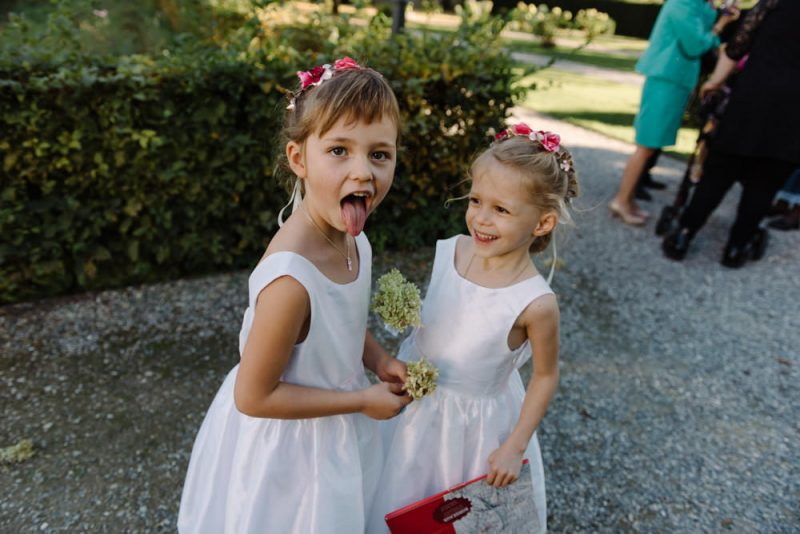 2 small bridesmaids sticking their tongues out for the camera.