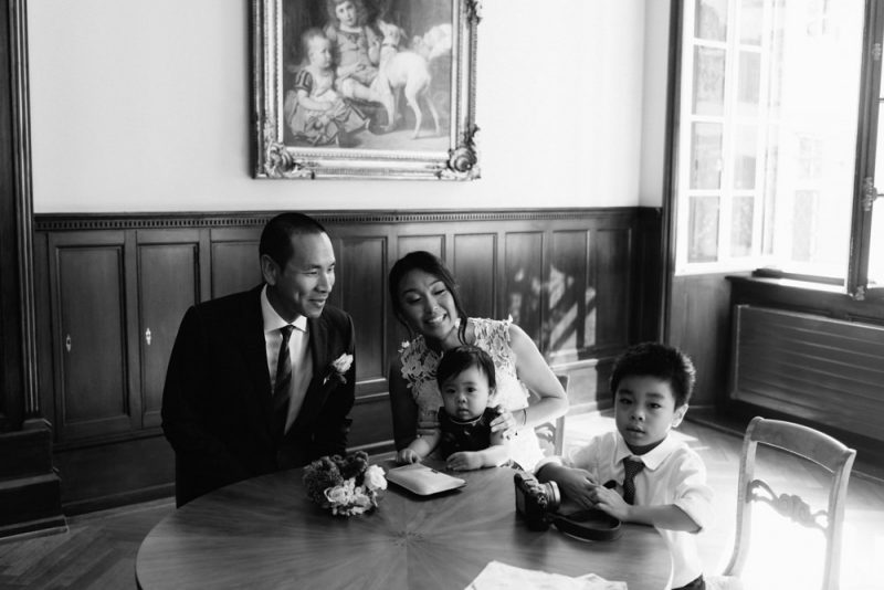 Bride and groom and their 2 small children wait in the waiting room of Basel Zivilstandsamt before their wedding, they are all smiling at each other. Wedding photography by Caroline Hancox Photography