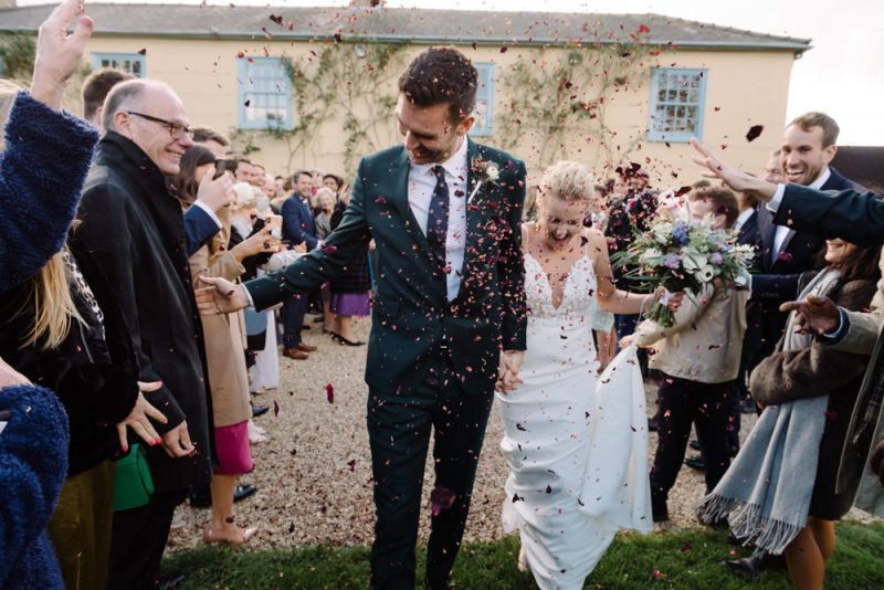 a couple walks through a tunnel of confetti. Groom is reaching out for his dads hand. You can see South Farm in the background
