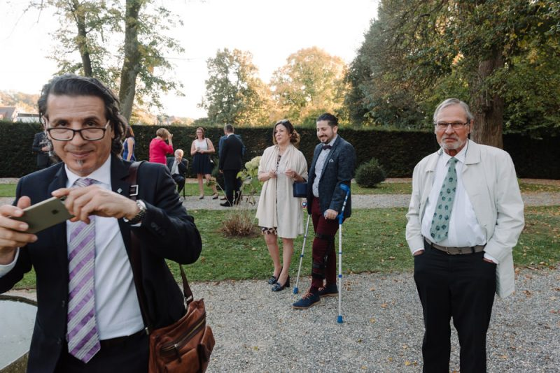 Guests at a wedding chatting and taking photos, 1 is caught offguard taking a photo and has a cheeky smile. they are in the ground of Schloss Bottmingen