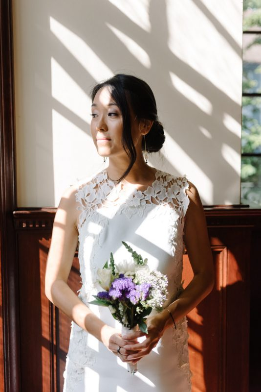 A beautiful bride is standing in front of a window and you can see the shadows of the window pains are falling on her. She is looking out the window and is holding a bouquet of flowers